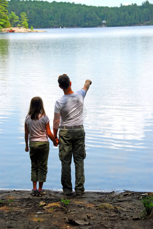 Father daughter lake stock photo, Father and daughter standing on the lake shore and looking at calm water, father pointing at somthing on the other shore by Elena Elisseeva