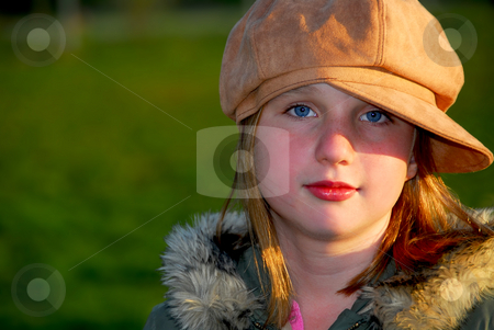 Girl portrait stock photo, Portrait of a young girl wearing suede hat on green background by Elena Elisseeva
