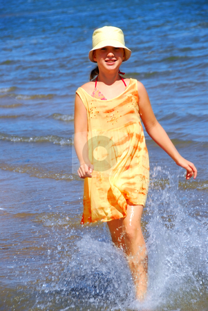 Running girl stock photo, Young girl running in a shallow water on a beach by Elena Elisseeva