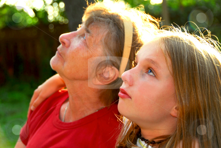 Two generations stock photo, Portrait of grandmother and granddaughter in summer park looking up by Elena Elisseeva
