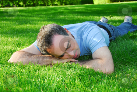 Man relaxing stock photo, Attractive man lying on green grass in a park relaxing by Elena Elisseeva