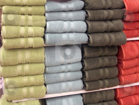 Rolls of towels stock photo, A variety of colorful bath towels are neatly displayed on the shelves inside a retail store. by Rebecca Mosoetsa