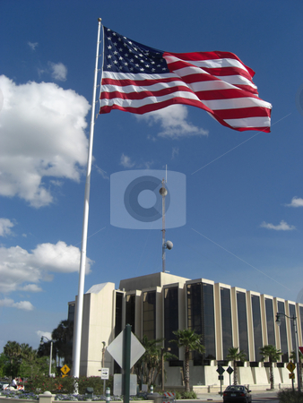 The Towering Flag stock photo, A flag stands tall above the ground, and is towering over a big building with a sattelite on the roof. by Rebecca Mosoetsa