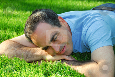Man on grass stock photo, A man lying on green grass relaxing by Elena Elisseeva