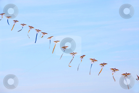 Kites in the sky stock photo, Many kites on one string in blue sky by Elena Elisseeva