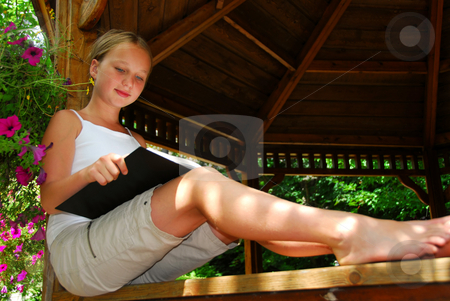 Girl read book stock photo, Young girl sitting in a gazeebo reading a book by Elena Elisseeva