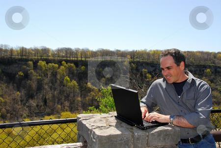 Smiling man working outdoors stock photo, Smiling man working outdoors, wireless concept by Elena Elisseeva