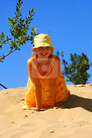 Girl dunes stock photo, Young girl in yellow hat sitting on top of a sand dune by Elena Elisseeva
