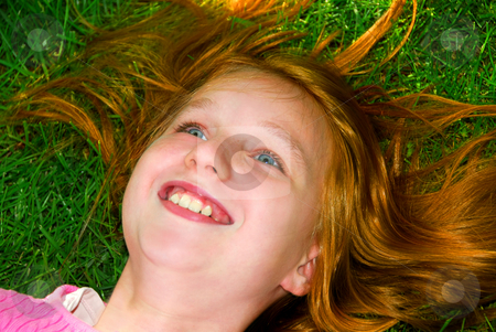Girl grass stock photo, Portrait of a young girl relaxing on green grass outside by Elena Elisseeva