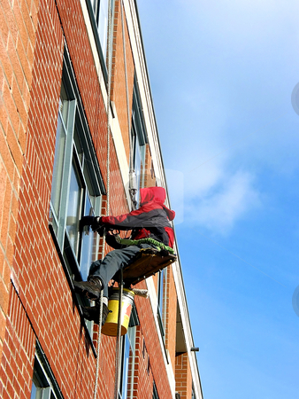 Window washer stock photo, Window washer working on a building wall by Elena Elisseeva