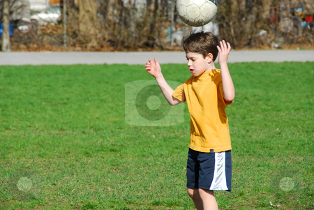 Boy with soccer ball stock photo, Little boy bouncing soccer ball on his head by Elena Elisseeva