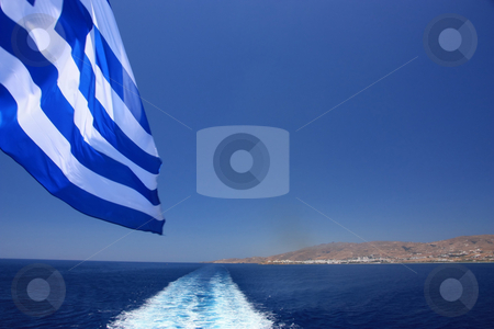Travelling in Greece stock photo, Watching the ship wake and the Greek flag (and the Greek island of Tinos in the far) by Georgios Alexandris