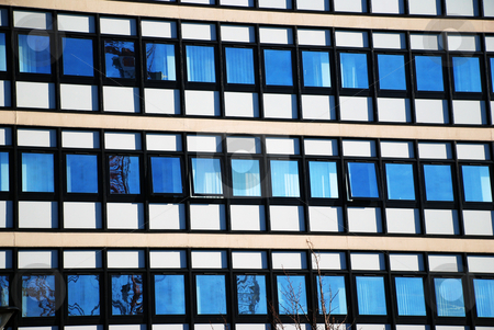 Modern Office Building with Window Reflections stock photo, A photograph of an example of modern architecture, with opposing buildings, the blue sky, and a construction crane in reflection. by Philippa Willitts