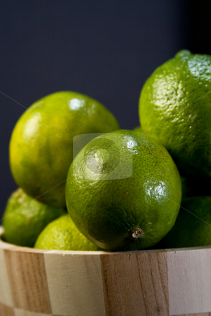 Limes in wooden bowl stock photo, A wooden bowl with multiple limes filling it up. by Jose Wilson Araujo