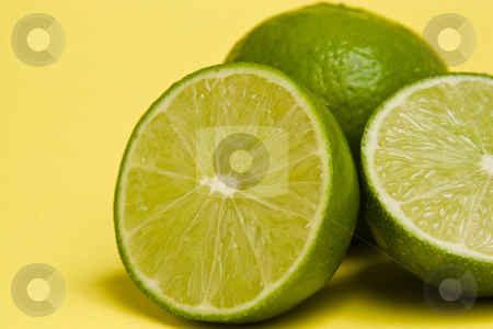 Sliced Lime stock photo, A lime sliced in half and a full lime in the background by Jose Wilson Araujo