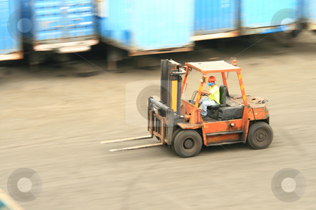 Forklift in motion stock photo, Orange forklift in motion at a  ship port by Jonas Marcos San Luis