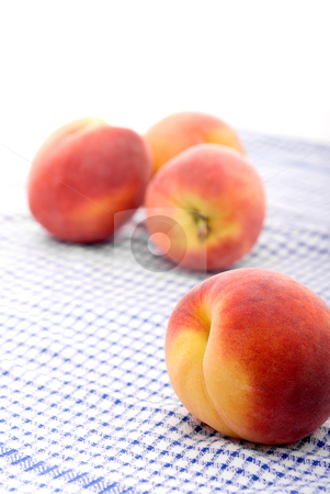 Fresh peaches on a kitchen towel stock photo, Shallow focus fresh peaches on a kitchen towel by Vince Clements