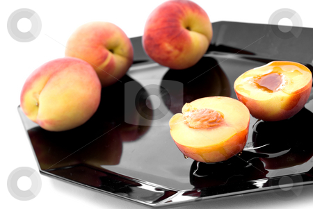 Fresh peaches with syrup on a black plate stock photo, Shallow focus fresh peaches with syrup on a black plate by Vince Clements