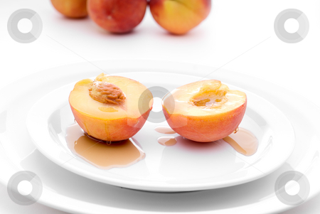 Fresh peaches with syrup on a white plate stock photo, Shallow focus fresh peaches drizzled with maple syrup on a white plate by Vince Clements