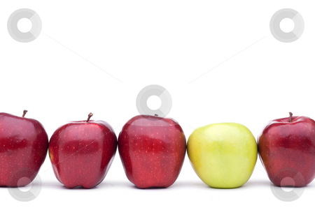 Red delicious apples with an individual green apple stock photo, Red apples lined up on a white background with a single different green apple by Vince Clements