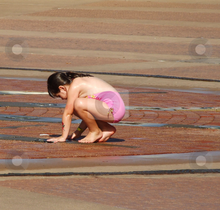Cooling Down stock photo, Young child crouches over sprinkler at a summer splash zone in an amusement park.  Summer fun by Marburg
