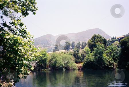 Hazy Summer Days stock photo, Lake surrounded by trees with Mountain in background.  Summer haze is clearly visible. by Marburg