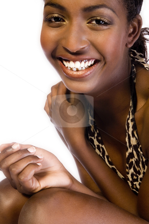 Dark female model showing her big smile stock photo, A beauty portrait taken from an african model in the studio showing her big smile by Frenk and Danielle Kaufmann