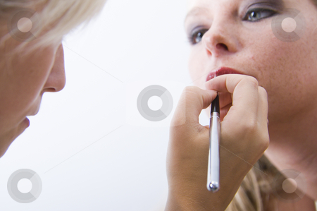 Model getting make up from her make up artist stock photo, Studio portrait of a beautyfull blond model with her make-up artist by Frenk and Danielle Kaufmann