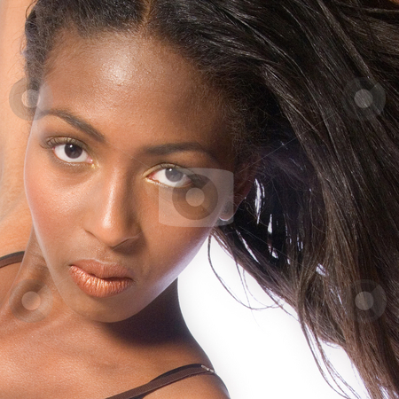 Dark female model making eye contact stock photo, A beauty portrait taken from an african model in the studio making eye contact by Frenk and Danielle Kaufmann