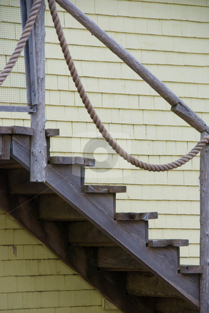 Maritime Staircase stock photo, Close up of an old wooden staircase on the side of a wooden house with yellow shingles by Maria Bell