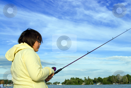 Fishing stock photo, Low angle view of a young girl fishing, shot against a cloudy sky by Richard Nelson