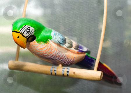 Wooden Parrot stock photo, A painted wooden parrot sitting on a perch by Richard Nelson