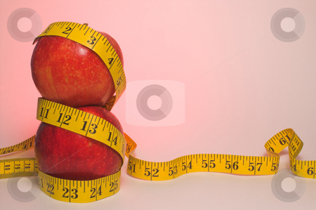 Diet Plan stock photo, Two red apples wrapped in a tailor's measuring tape. by Robert Byron