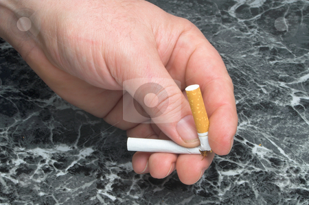 Quit Smoking stock photo, A person breaking a cigarette, signifying that they are quitting smoking. by Robert Byron