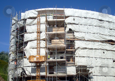 Modern Building Site stock photo, A general view of the exterior of a new modern building site development covered in scaffolding and cladding. by Martin Crowdy