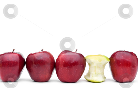 Red delicious apples with an individual green eaten apple stock photo, Red apples lined up on a white background with a single eaten green apple by Vince Clements