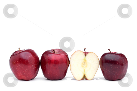 Red delicious apples with one sliced apple stock photo, Red apples line up on a white background with one sliced apple by Vince Clements
