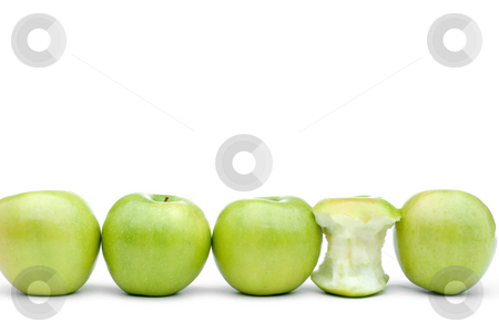Fresh green apples with one eaten apple stock photo, Green apples line up on a white background with one eaten apple by Vince Clements