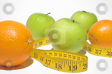 Weight Loss Concept stock photo, A tailor's tape snaking through apples and oranges. by Robert Byron