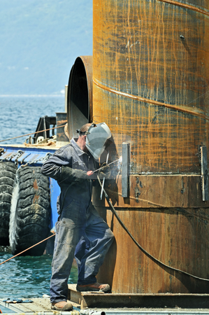 Welder stock photo, Worker using soldering iron on a rusty pylon in a harbour by Massimiliano Leban