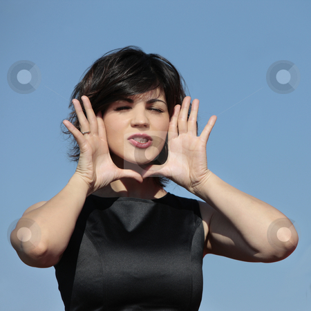 Woman shouting with hands around her face stock photo, Young attractive girl with her hands as a frame around her face shouting outdoors by Claudia Veja