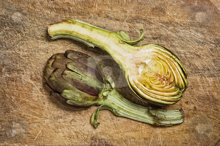Two artichokes  stock photo, Two artichokes on a wooden cutting table. by Pablo Caridad