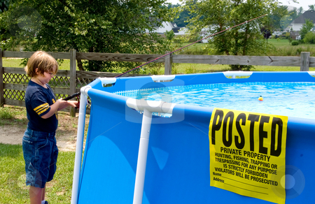 Posted No Trespassing stock photo, Boy fishing in a swimming pool with a no trespassing sign. by Robert Byron
