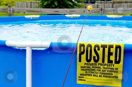 Posted Property stock photo, A posted sign on a swimming pool next to a fishing pole. by Robert Byron
