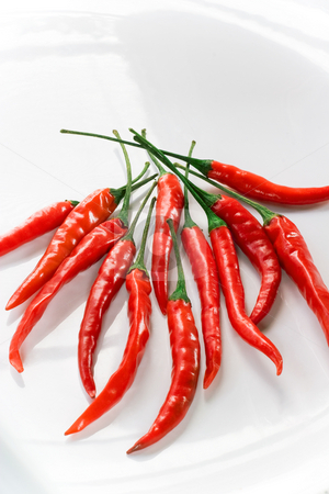 Red Hot Chili Cayenne Peppers on White Plate stock photo, Multiple peppers grouped on shiny plate by Mark S