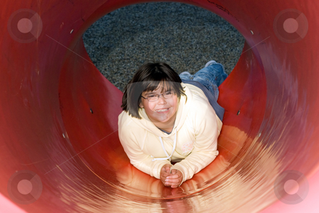 Playtime stock photo, A young girl playing on a red slide in a park by Richard Nelson