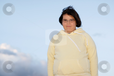 Girl with sky background stock photo, Low angle view of a young girl standing against the sky representing success by Richard Nelson
