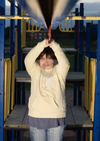 Playground Girl stock photo, A young girl playing on some playground equipment by Richard Nelson