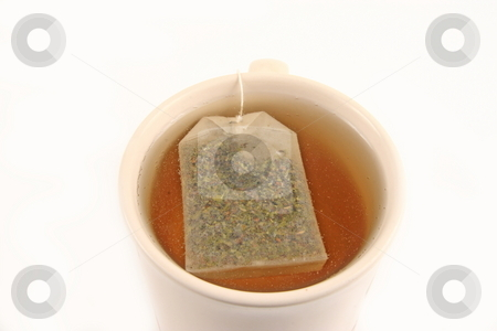 Tea stock photo, Green tea bag in a cup brewing on white background by Jack Schiffer
