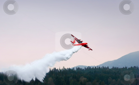 Red And White Water Bomber Fights Fire Over Forest stock photo, Water bomber drops water on forest against darkening sky by Mark S